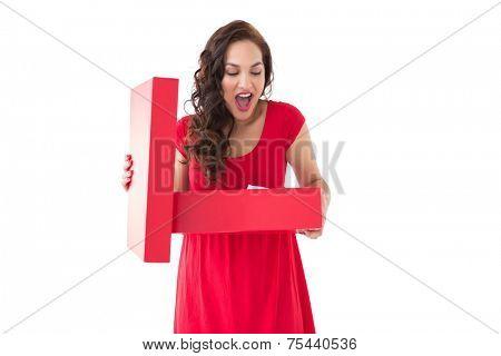 Astonished brunette holding a box on white background