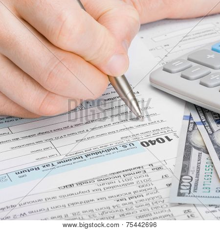 Male Filling Out 1040 United States Of America Tax Form