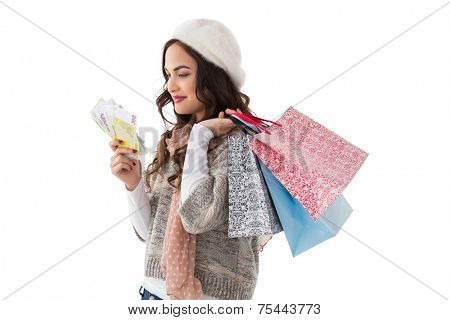 Happy brunette holding cash and shopping bags on white background