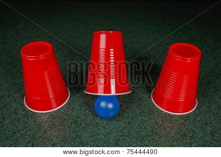 Three Red Cups And A Blue Ball