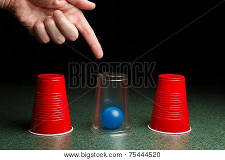 Blue Ball Under Clear Cup With Hand