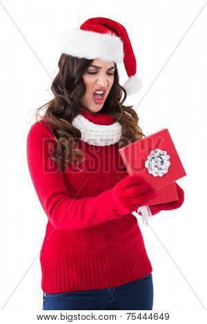 Disappointed brunette opening christmas gift on white background
