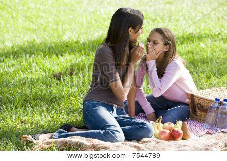 Girls Whispering On Picnic Blanket On Grass In Park