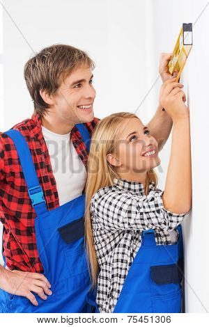 Repairman helping woman to use builder level