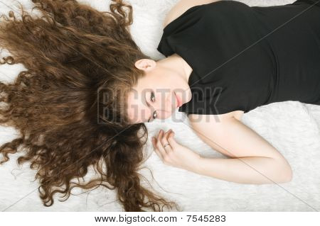 Happy Young Woman With Nice Long Curly Hair On White Fur. Brunet, Brunette