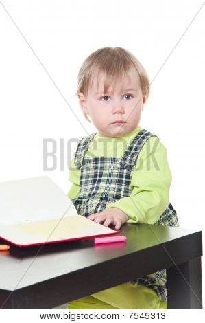 The Little Girl Sits At A Table And Does A Homework, Draws In A Notebook. It Is Isolated On A White