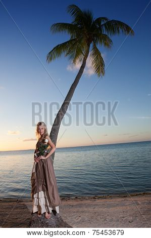 The young woman in a long sundress on a tropical beach. Polynesia.