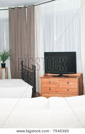 The Big Tv In A Room Before A White Sofa