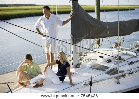 Father And Two Teenage Children Relaxing On Boat