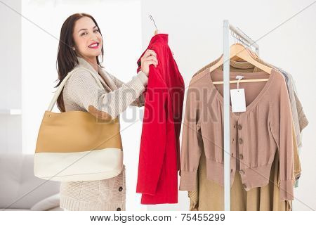 Pretty brunette picking out jacket at clothes store