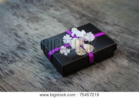Black gift box with white flowers on the old wooden background.