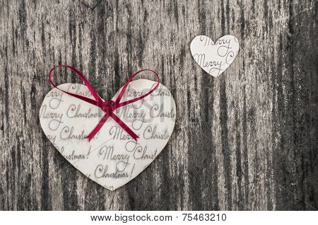 Heart shaped paper Christmas ornaments with a red bow on a rustic wood background