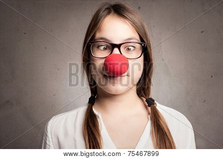 happy young girl with a clown nose