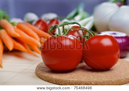 Tomatos with vegetables on a background