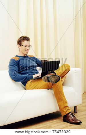Portrait of a goodlooking smiling young man sitting on a couch at home and working on his laptop.