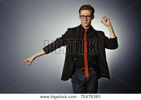 shot of a handsome young man in elegant black suit posing with expression. Studio shot.