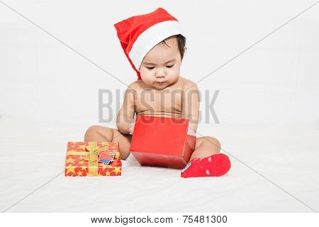 Asian Baby With Christmas Cap Pick Up Something In Gift Box