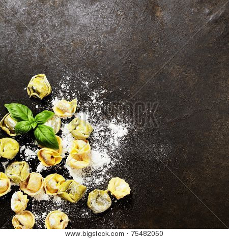 Homemade raw Italian tortellini and basil leaves on dark vintage background