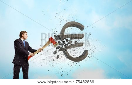 Young determined businessman crashing euro sign with axe