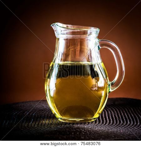 sunflower oil in a jug on brown background