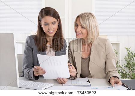 Female senior and junior managers sitting at desk working together in a business team.