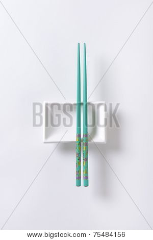 pair of blue chopsticks and white bowl on white background