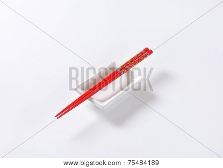 pair of red chopsticks and white bowl on white background