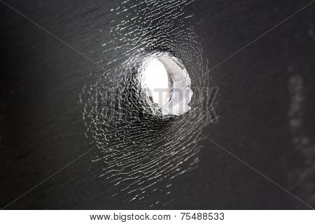 Bullet hole in thick sheet metal side view