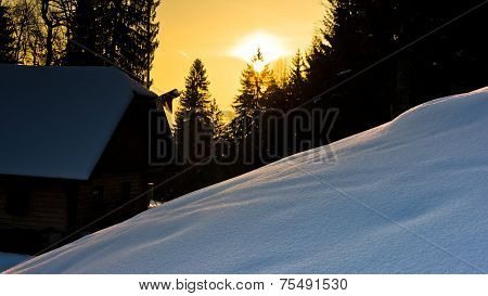Sunrise reflections on a snow in front of mountain hut