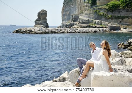 Couple Smiling And Relaxing Near The Sea, Naples, Italy