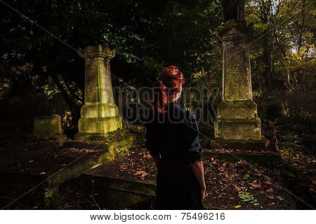 Young Redhead Woman Standing In Cemetery