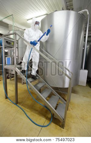 worker in white protective uniform,mask,gloves with high pressure washer on stairs at large industrial process tank preparing to cleaning