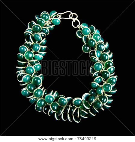 Bracelet with Green Gemstones and Gold, Isolated on Black Background