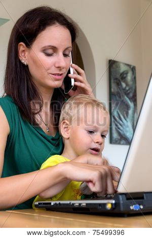 a young woman working at home in a home office and has a child by her side