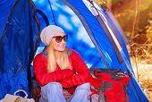 stock photo of tent  - Happy smiling camper girl sitting in the tent - JPG
