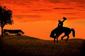 picture of bucking bronco  - Sunset silhouette of a cowboy riding a bucking horse - JPG