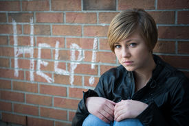 stock photo of school bullying  - Sad, depressed girl outside school, with red brick background, asks for help