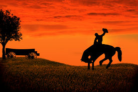 foto of bucks  - Sunset silhouette of a cowboy riding a bucking horse - JPG