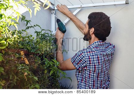 man using cordless battery drill for outdoor home improvements