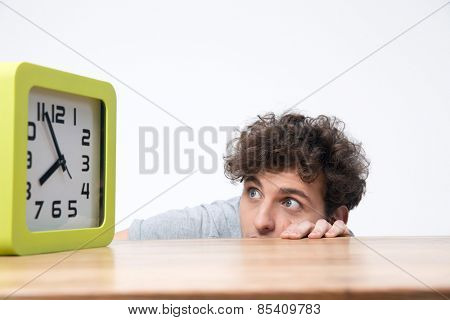 Young man sitting at the table and looking on the big clock