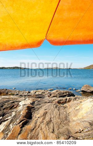 Swedish Coast With Orange Parasol And Blue Ocean
