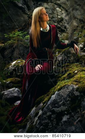 woman fairy with long blonde hair in a historical gown is sitting amids moos covered rocks