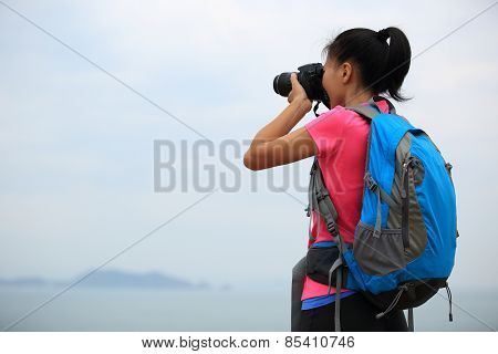 woman hiker photographer taking photo at seaside mountain peak