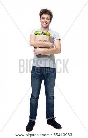 Full length portrait of a cheerful man holding a bag full of groceries