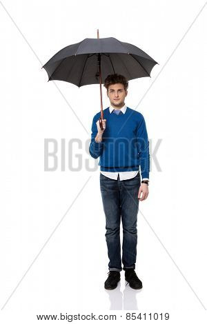 Full length portrait of a businessman standing under umbrella