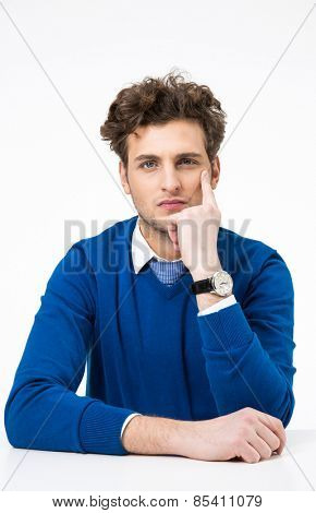 Young pensive businessman sitting at the table