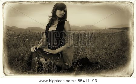 beautiful girl in a historical costume sitting on a meadow with her head slightly turned