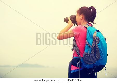 woman hiker photographer taking photo at seaside mountain peak
