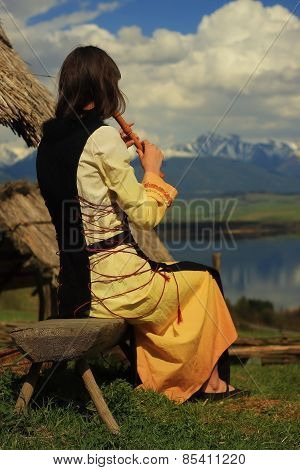 beautiful girl in a historical costume playing her flute in an open landscape with a lake
