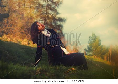 young woman with dark hair and a historical dress posing on a meadow in open lanscape